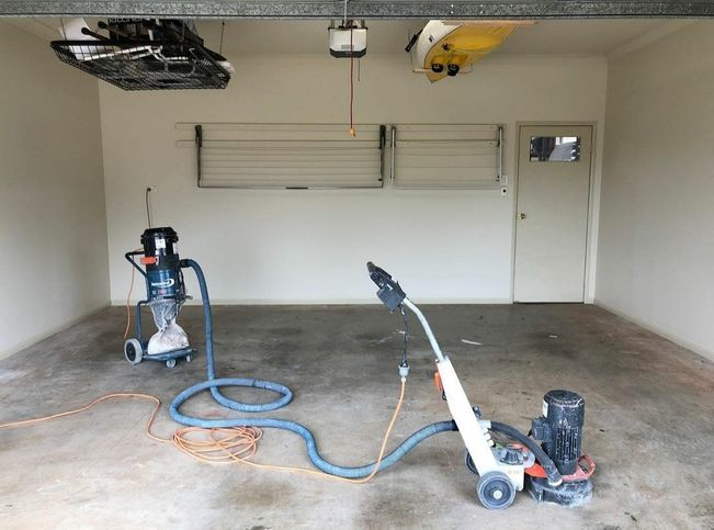 Concrete floor grinding and preparation prior to floor laying in garage with epoxy concrete coating
